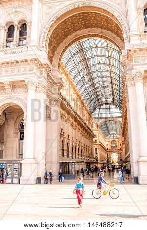 Milan, Italy - June 06, 2016: People walk on Duomo square near the famous Vittorio Emanuele shopping gallery in the center of Milan city.