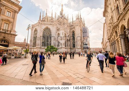 Milan, Italy - June 06, 2016: People walk on the square near the famous Duomo cathedral in Milan city in Italy. City life in the center of Milan