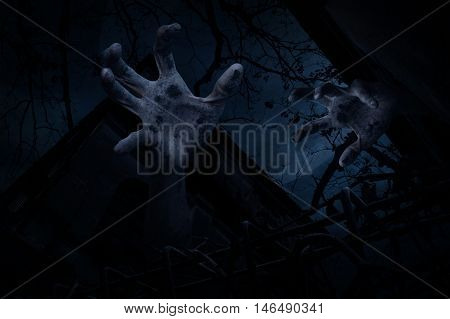 Zombie hand rising out from old grunge castle over dead tree moon and cloudy sky Spooky background Halloween concept