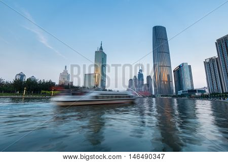 a pleasure boat motion blur on the beautiful haihe river in tianjin central business district at dusk China