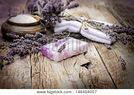 Lavender soap and scented salt on rustic wooden background - spa concept (treatment)