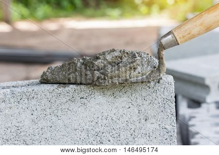 Cement or mortar Cement mix with a trowel put on the brick for construction work.