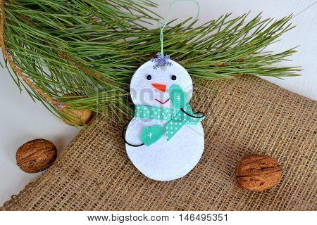 Fun felt snowman. Christmas tree ornament. Christmas tree branch, walnuts