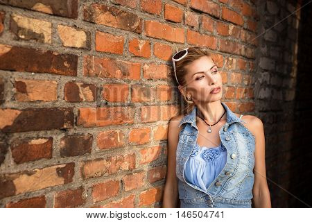 fashion portrait of a girl at a brick wall