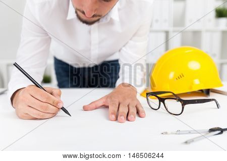 Bearded engineer working at blueprint in his white office making corrections. Yellow hard hat glasses and compass lie on table. Concept of mistake in calculations.