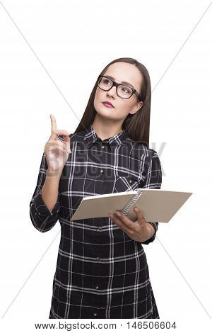Isolated portrait of nerd girl in dress holding a book and pointing up with her finger. Concept of know it al. Mock up