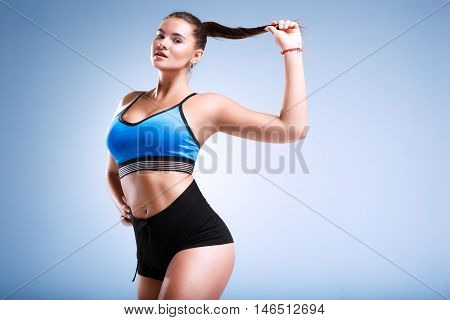 Modep plus size is posing in a studio on a blue background in underwear