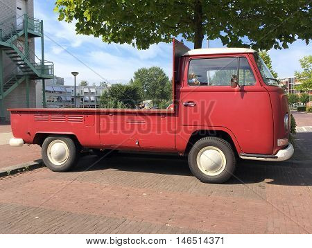 Almere, The Netherlands - September 10 2016: Red Volkswagen Transporter Pick-Up Truck on a public parking lot in the city of Almere. Nobody in the vehicle.