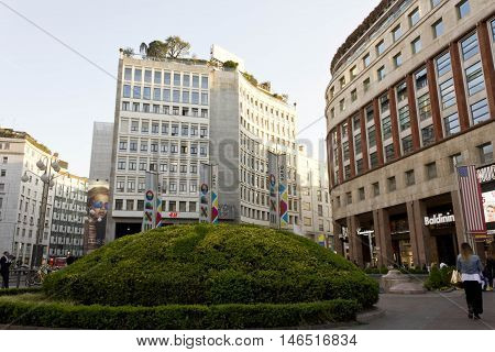 MILAN, ITALY - APRIL 13 2015: Buildings in Piazza San Babila square in Milan at day time with an edge in the foreground