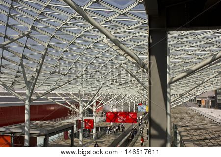 MILAN, ITALY - APRIL 15 2015: Architectural view of the covered glass roof of Fiera Milano during Salone del Mobile fair in Milan with people around