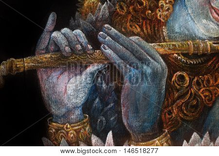 hands of lord krishna playing flute, detail with lotus pattern.