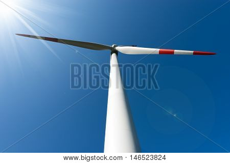 Detail of a white and red wind turbine with sun rays on a clear blue sky
