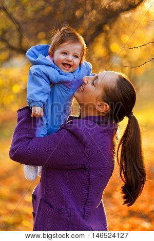 Portrait of mother and baby boy in the park in the autumn. Laughing at each other