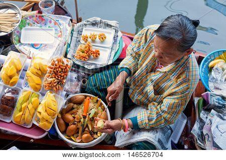 Damnoen Saduak Thailand - March 21 2011 - Senior Thai woman selling freshly cooked food and fruits on a boat in Damnoen Saduak Floating Market