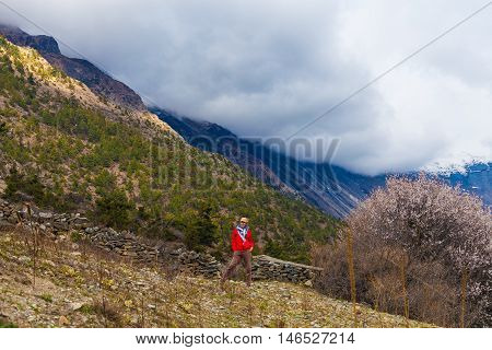 Portrait Young Pretty Girl Wearing Red Jacket Himalays Mountains.Asia Nature Morning Volcano Viewpoint.Mountain Trekking, View Landscape.Woman Happy Smiling.Horizontal picture.First Rays Rising Sun