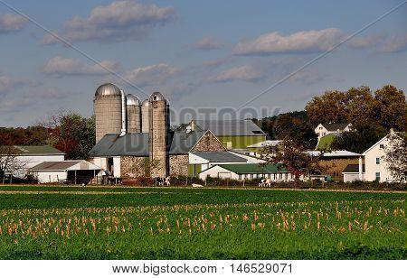 Lancaster County Pennsylvania - Ocrober 15 2015: Amish farm complex with farmhouse, barns, silos, and a field of harvested cornstalks