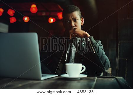 Indoor portrait of young black man sitting in cafe, drinking coffee or tea and working with lap top. Model looking at camera. Toned.