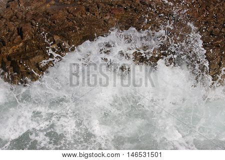 This is a close up image of waives against the rocks at high tide at Asilomar Beach in Pacific Grove, California.