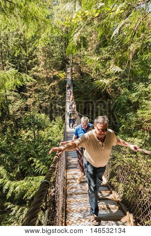 North Vancouver, Canada - 2016: People walking on Lynn Canyon Suspension Bridge