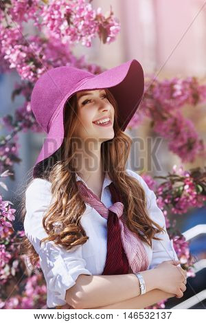 Outdoor portrait of young beautiful happy smiling lady posing near flowering tree. Model wearing stylish accessories and clothes. Girl looking aside. Female beauty and fashion concept. City lifestyle.