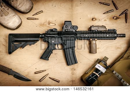 Assault rifle and bullets on a wooden table