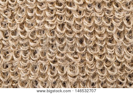 Loops of rough flax fabric. Natural flax fibres are processed to a coarse fabric, used for massage straps and gloves. Solid yarn with brown ochre color. Isolated macro photo close up.