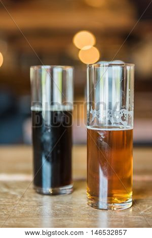 Two small glasses of beer for tasting in rustic room with pale ale and dark stout
