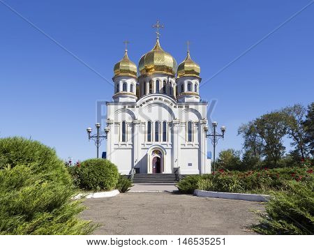 Orthodoxy church temple with golden domes: Holy Protection of the Mother of God. Front view. Greenery and blue sky. Donetsk, Ukraine, 2016.