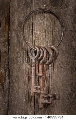 Bunch of old keys on a wooden background