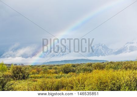 Grand Teton mountains covered with fog and dark storm clouds with rainbow