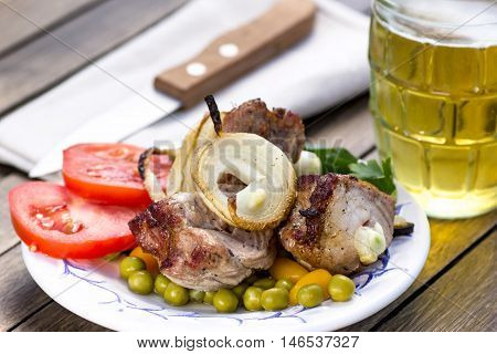 Portion of grilled shashlik with vegetables on plate and beer