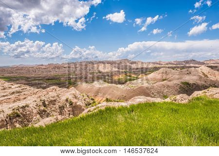 View of eroded Badlands canyons with green prairie valley and shadows from dark storm clouds