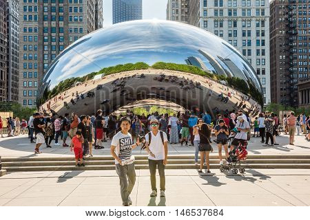 Chicago, USA - May 30, 2016: Chicago bean in Millennium Park with many people and buildings in background and two young guys taking a picture