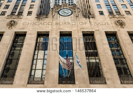 Chicago, USA - May 30, 2016: Closeup of Board of Trade Building along LaSalle street in Illinois with a clock, two clerks and an eagle sculpture