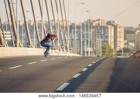 Skateboarder Riding A Skate And Doing Jumps On The City Road Bridge. Free Ride Skateboards