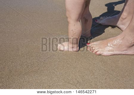 Mother and baby feet walking on sand beach for first time