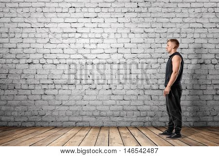 Front view of muscled young man standing, on the background of white brick wall. Wellbeing. Muscleman. Workout and fitness.