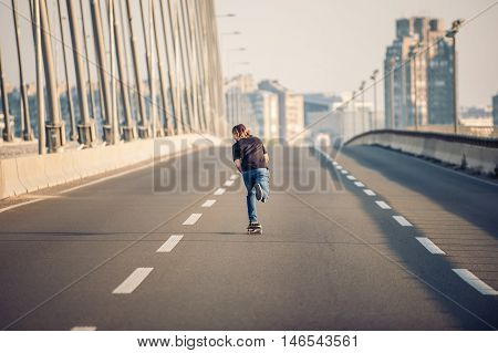 Skateboarder Riding A Skate Over A City Road Bridge. Free Ride Skateboards