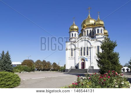 Orthodoxy church temple with golden domes: Holy Protection of the Mother of God. Angle view. Greenery with red roses and blue sky around it. Donetsk Ukraine 2016.