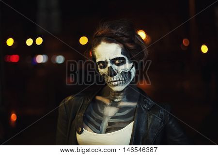 Young woman with Halloween face art. Street portrait. Night city background. Close up.