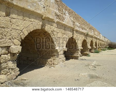 A roman built aqueduct in Israel beside the sea.