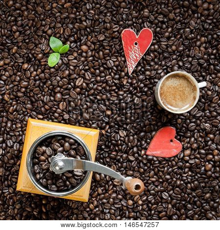 Roasted coffee beans as a background of coffee grinder and cup of fresh coffee