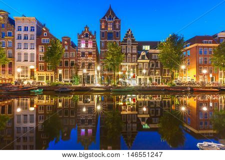 Night city view of Amsterdam canal Herengracht with typical dutch houses and their reflections, Holland, Netherlands.
