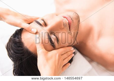 Happy young man is getting facial massage by professional masseuse. He is lying and smiling