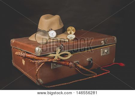 Travel and advanture concept. Vintage brown suitcase with clock, fedora hat, bullwhip, compass, magnifying glass and ankh key of life on dark background.