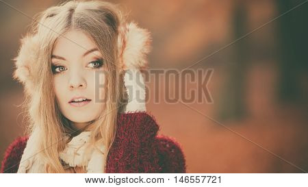 Portrait of pretty attractive fashionable woman in fall forest park. Gorgeous young girl in earmuffs and maroon sweater pullover. Autumn winter fashion. Instagram filter.