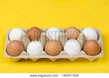 Tolerance concept. Brown eggs among white eggs in box on yellow background.