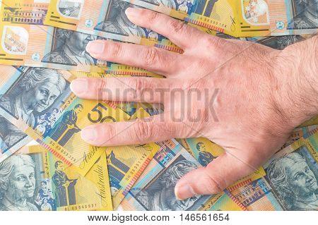 Caucasian Man Hand on Australian Dollar Banknotes