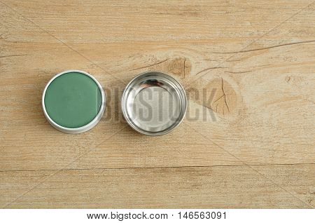 A green ointment in a white tin with a silver lid isolated on a wooden background