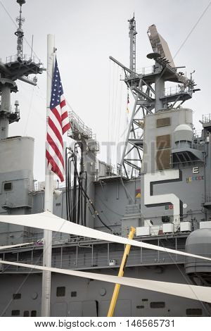 NEW YORK MAY 30 2016: The American Flag in front of the USS Bataan (LHD 5) at Pier 88 at the Memorial Day Commemoration ceremony on the Intrepid Sea Air & Space Museum during Fleet Week NY 2016.
